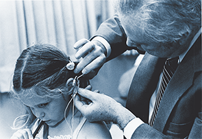 William F. House, MD, with Tracy Husted, the first pediatric cochlear implant patient (Los Angeles, 1981).