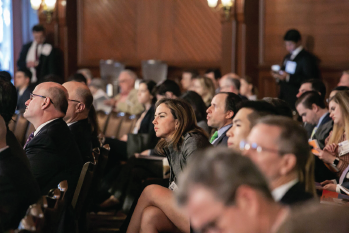 Audience members watch a presentation at the Triological Society Combined Sections Meeting.