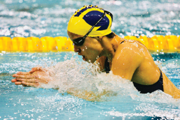 Dr. Silva Merea competing in a breaststroke event for the University of Michigan.