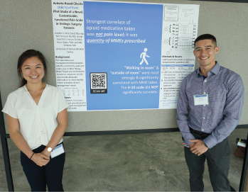 Medical students Jennifer Li and Vincent Bo with their minimalist poster at the Midwest Regional Pain Interest Group Meeting in Kansas City, Kansas. Interested viewers can scan a QR code with their smart device to get more information about a poster or its authors. Credit: Jennifer Villwock, MD