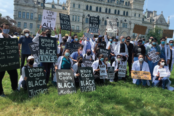 University of Connecticut otolaryngology residents David Wilson, MD, and Roshansa Singh, MD, (standing second and third, from right, respectively) and Lawrence Kashat (seated row, second from right) participating in the White Coats for Black Lives movement during the June 6, 2020, BLM March in Hartford, Conn.