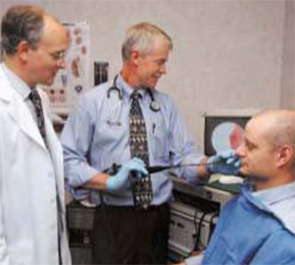 Drs. Smith (right) and Elstad (left) perform a flexible bronchoscopy on a patient who is unsedated